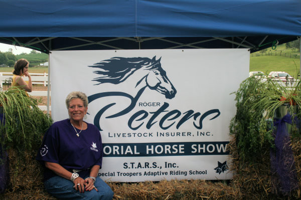 Conni Peters sitting next to the Roger Peters Livestock Insurer, Inc. Memorial Horse Show Banner.